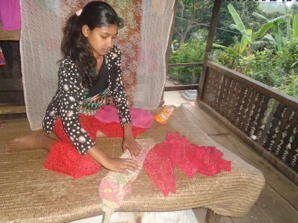 Nepalese girl folding clothes
