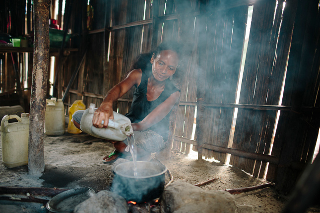 Timor-Leste – Woman cooking indoor with woodfire