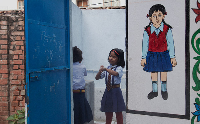 Two Indian school girls utilise new hand washing facilities