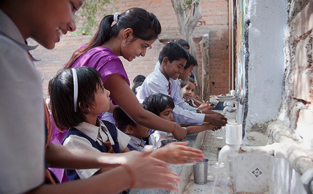 Teacher demonstrates the use of new hand washing facilities in an Indian school