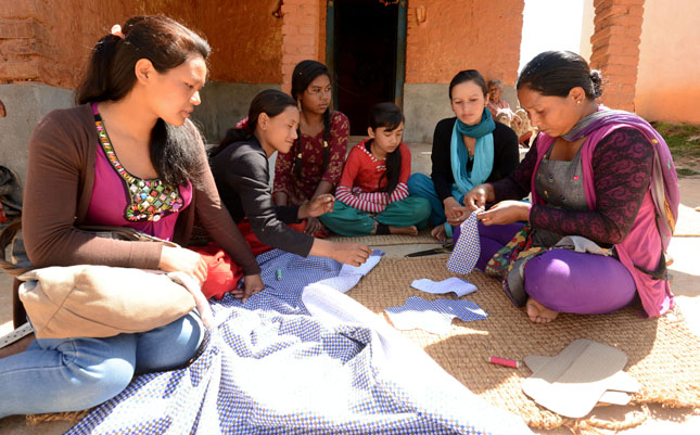 Women sitting in a circle cutting fabric