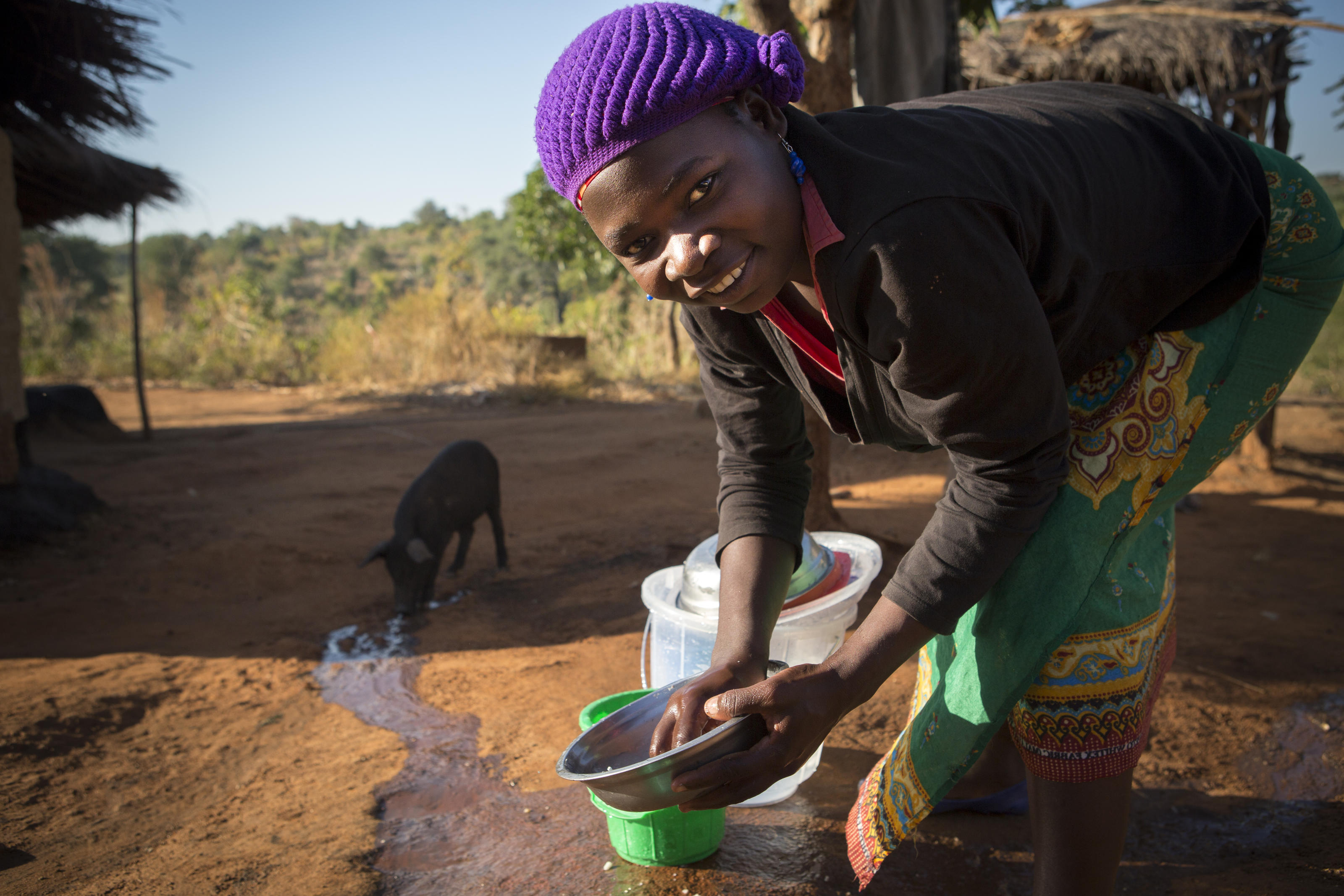 Zione washes dishes with clean water outside her home in the village of Chandaka, Malawi.