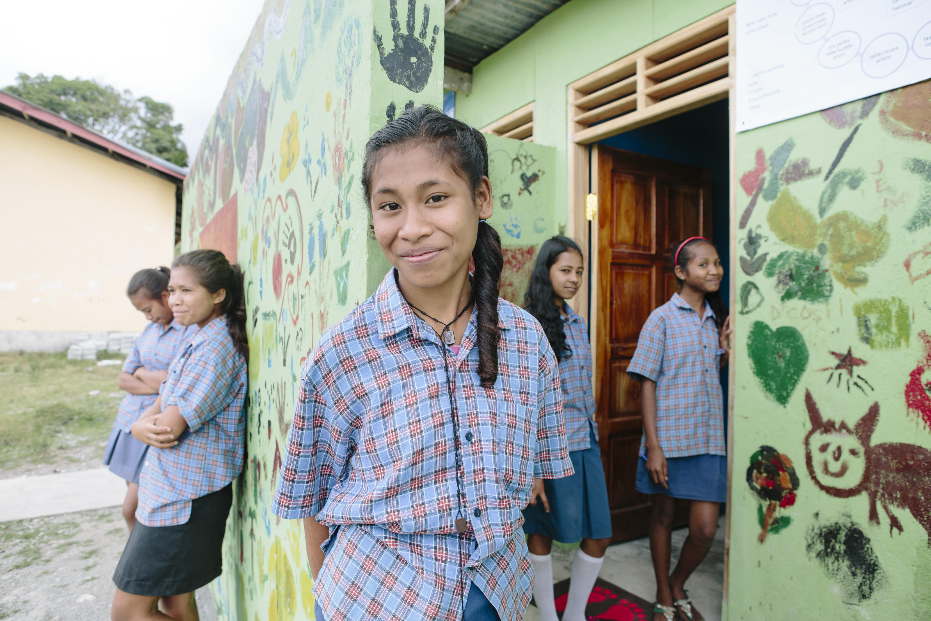 Etelvina Vita Da Costa, 15 (centre), outside the new toilet block at Ailuli Pre-Secondary School in Same, Manufahi District, Timor-Leste, 2015