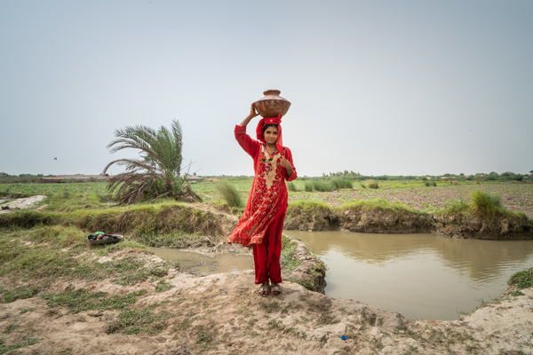 A young woman carries water on her head next to a dirty water source