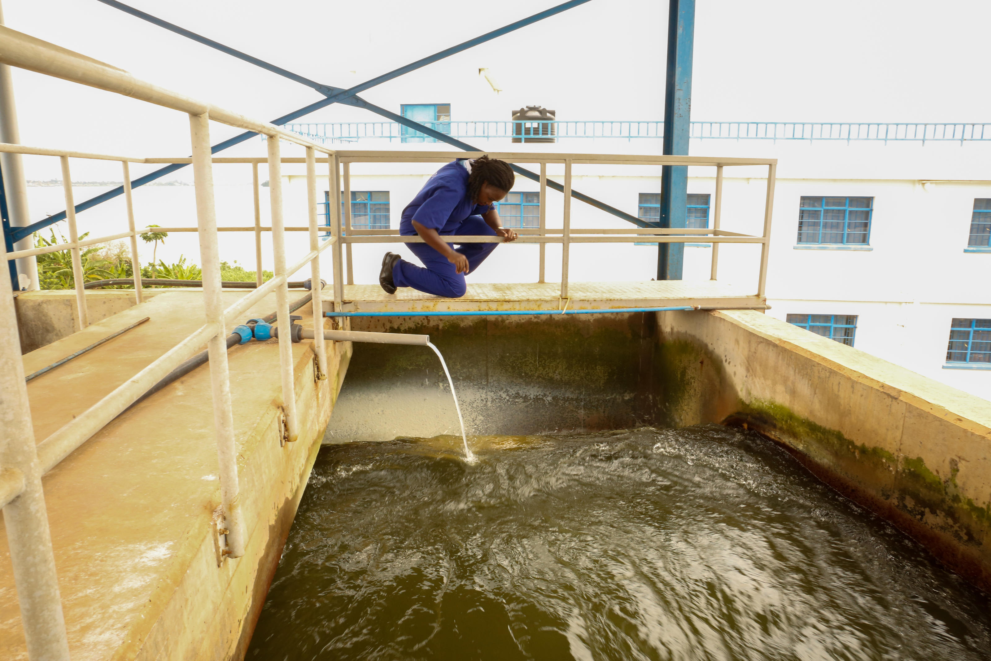 Kaggwa Lillian, senior shift overseer at the National Water and Sewage Corporation, observing the different stages of water treatment at Gaba Water Works, Kampala, Uganda, February, 2019.