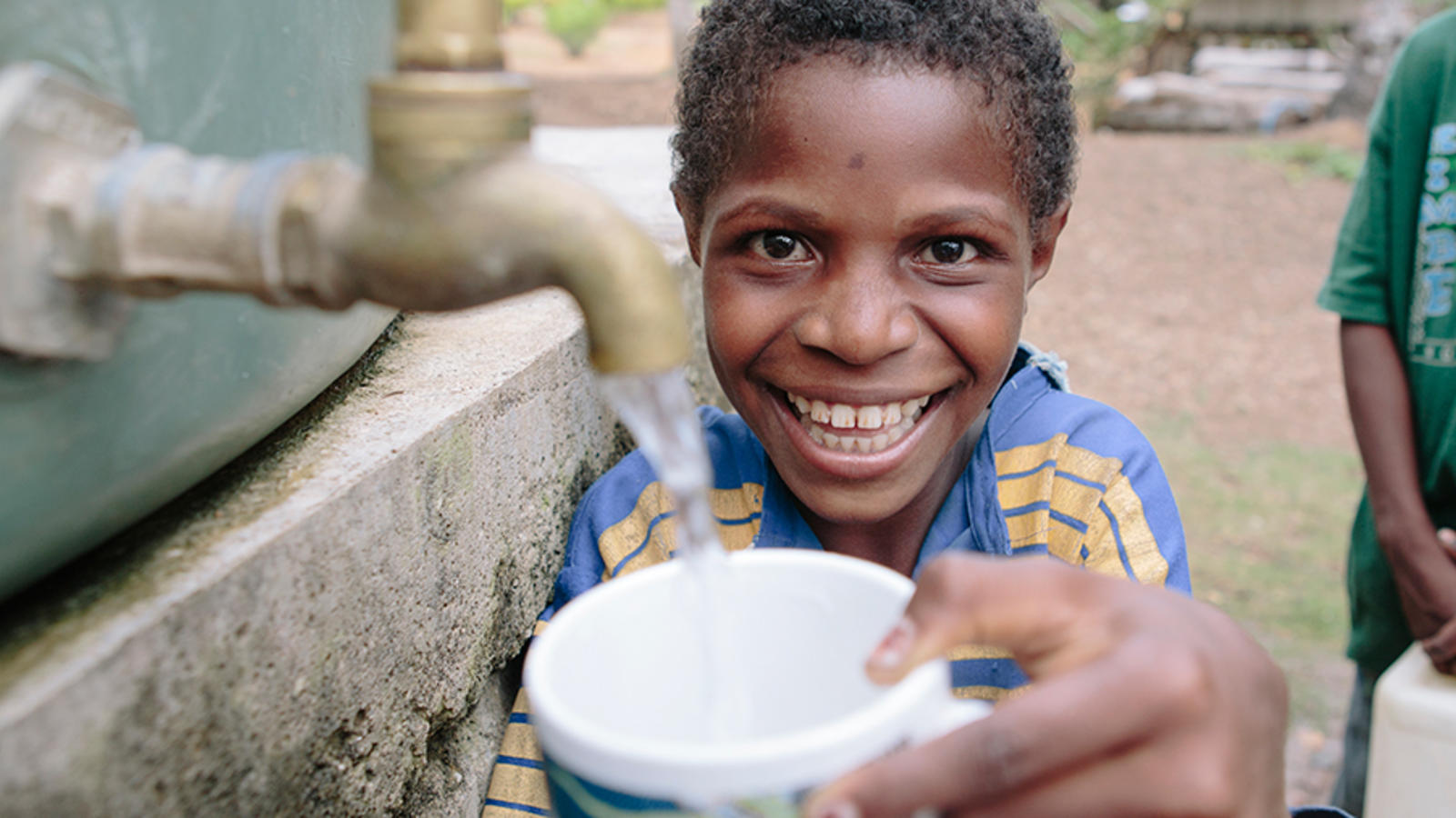 Papua New Guinean boy filling cup with water from a tap.