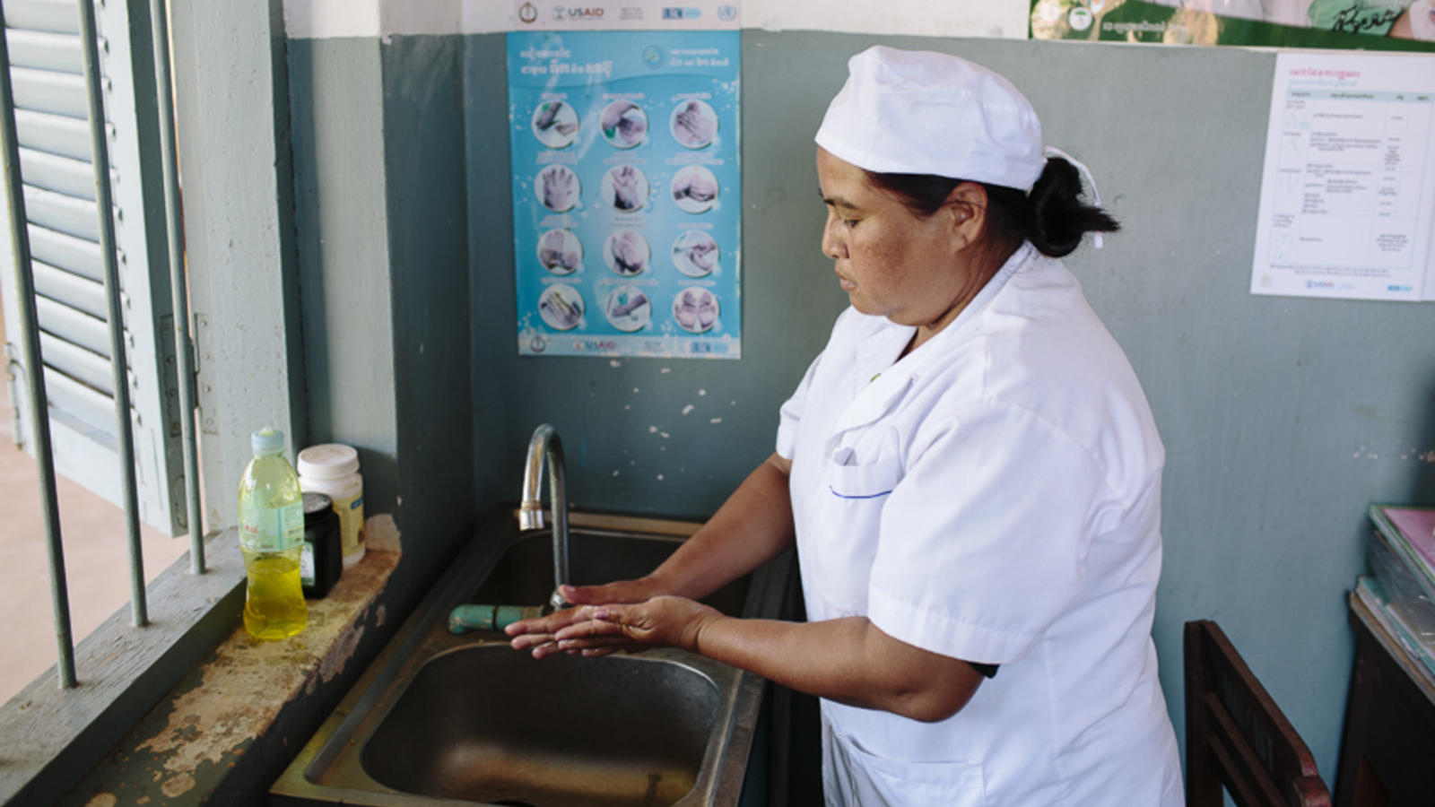 Midwife washes her hands at a sink, Cambodia