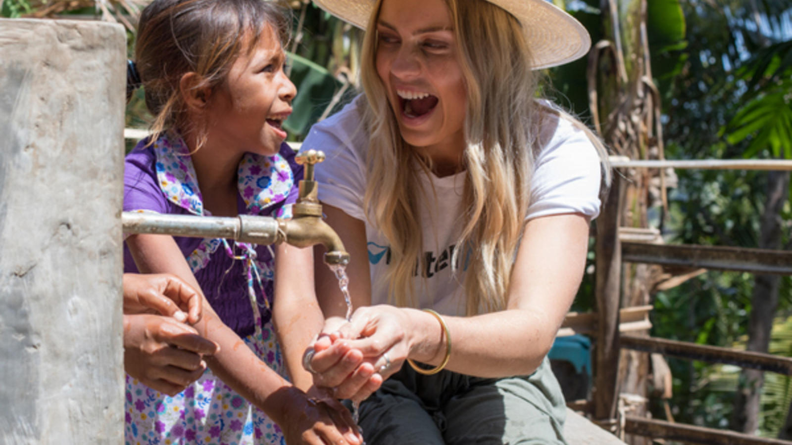 Elyse Knowles with a kid a tap in Timor-Leste