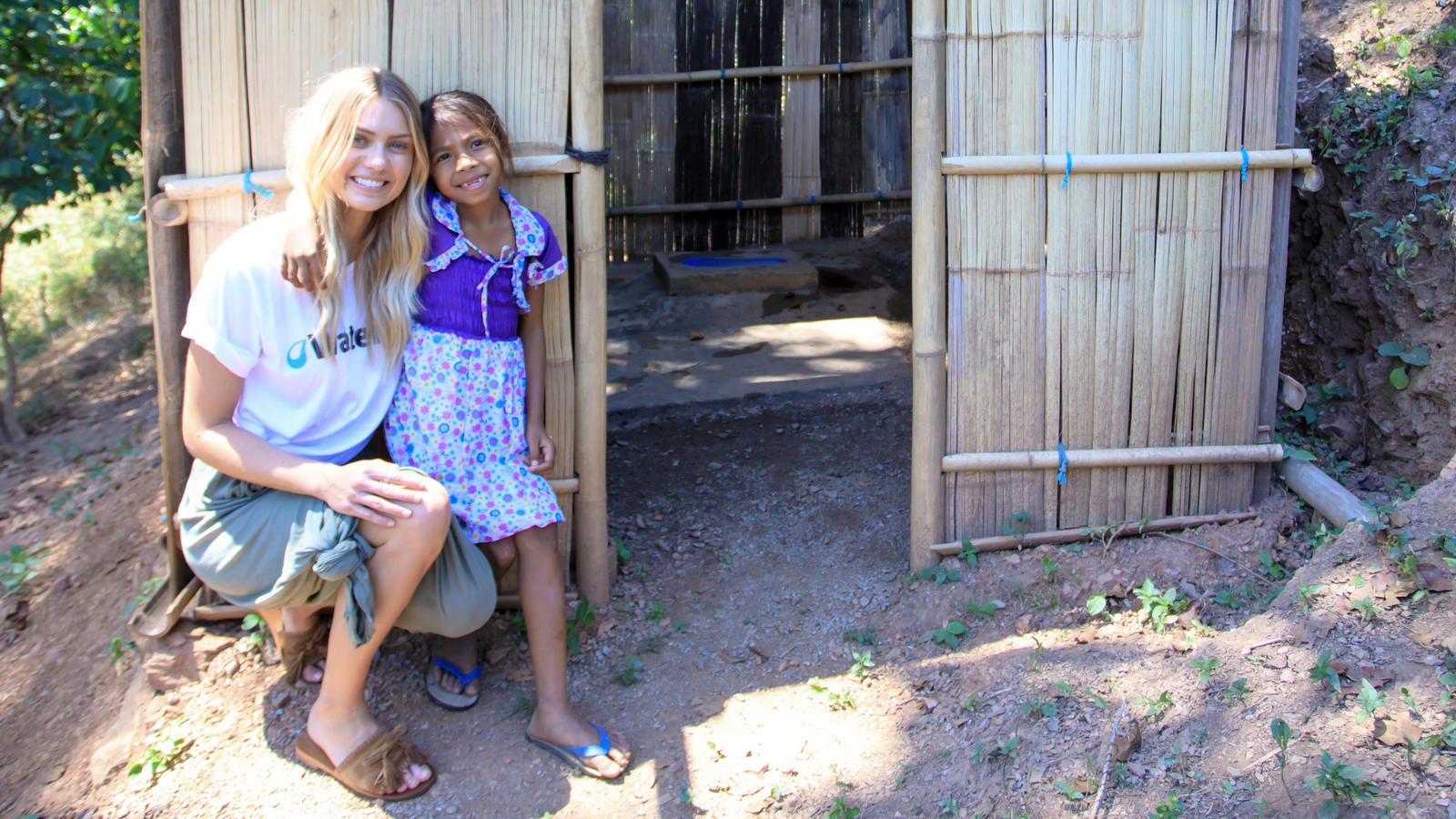 Elyse Knowles with a young girl in front of a toilet block in remote Timor-Leste