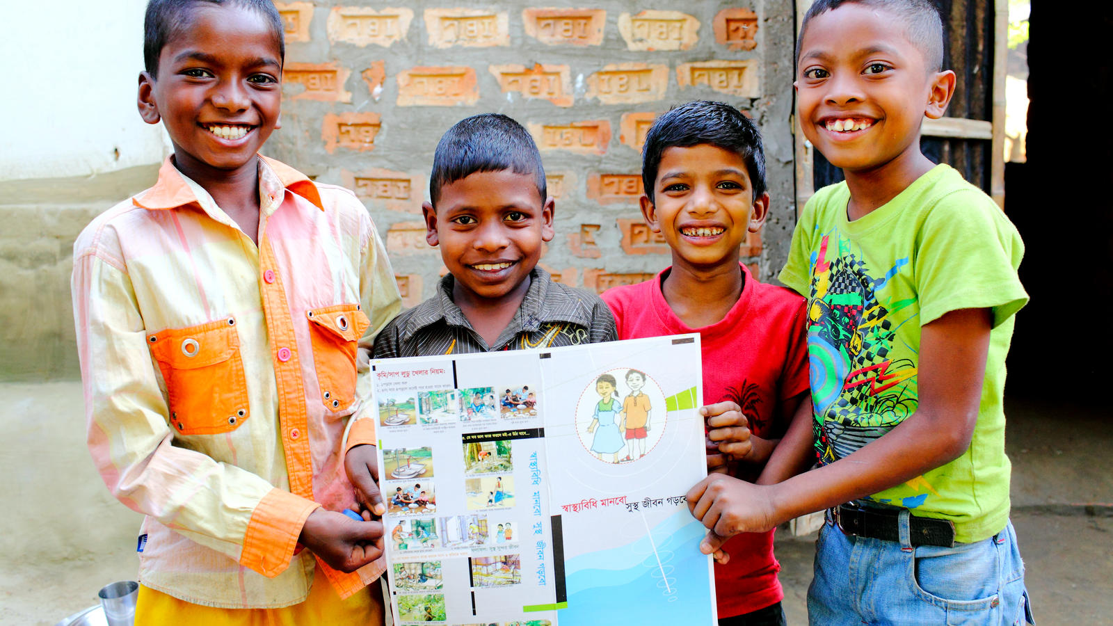 A group of children hold a hygiene education poster in Sylhet, Bangladesh.