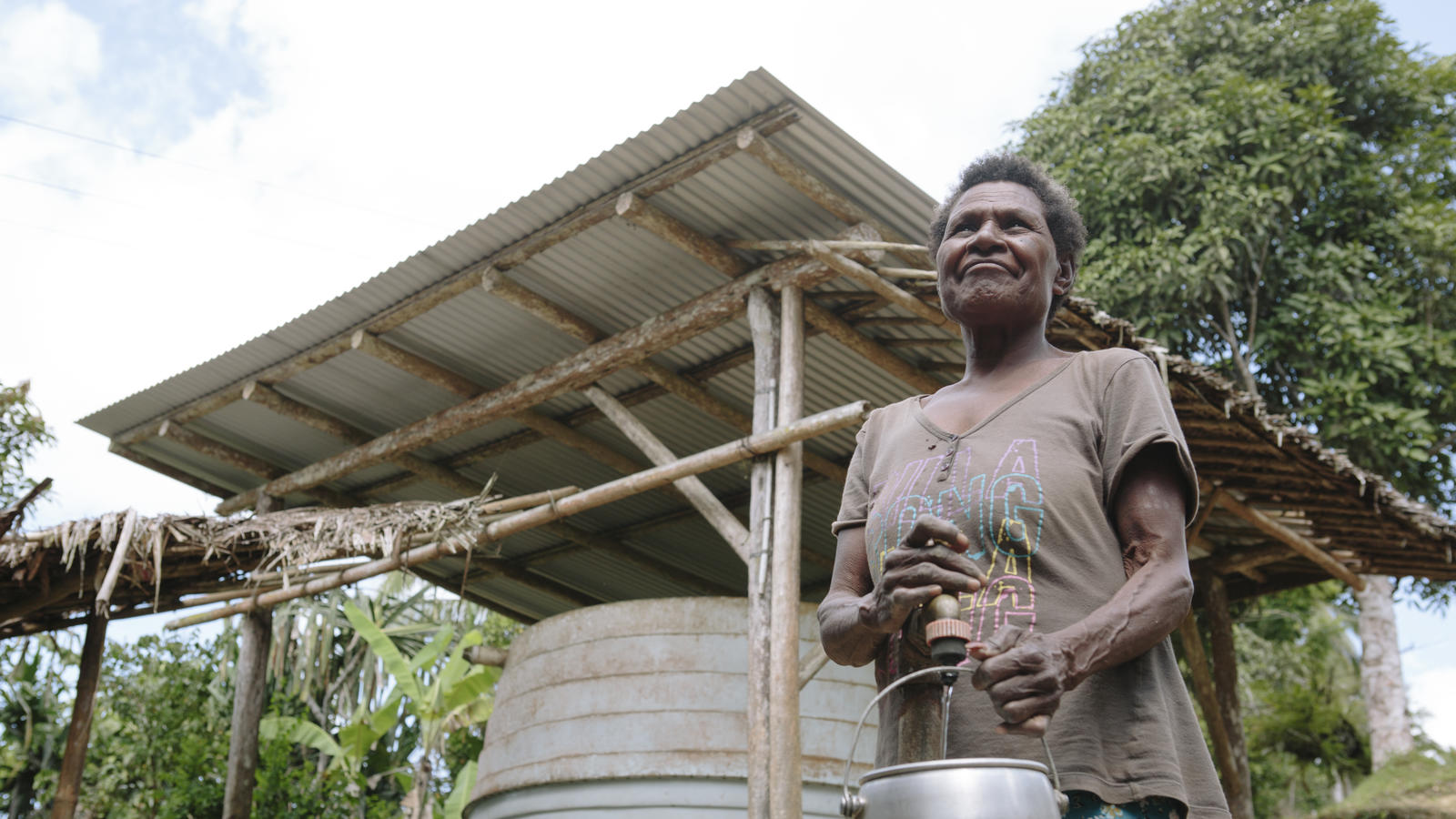 Anastasia Fingu, 64, collecting clean water from her water tank, Anastasia was the first person in the village to get a water tank through a council donation, it helps her feed her chickens, Simbrangu village, East Sepik province, Papua New Guinea, 2013