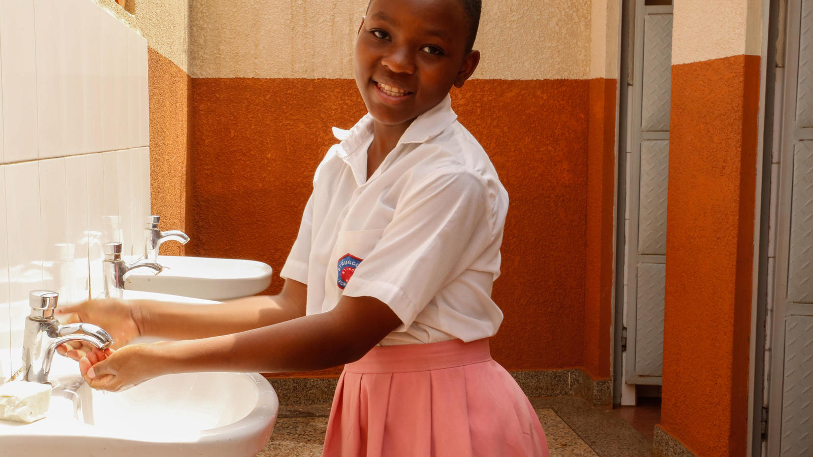 Catherine, 13, student, washing her hands at a newly installed sink in the girls' toilet block, Ntinda Primary School, Kampala, Uganda, February, 2019.
