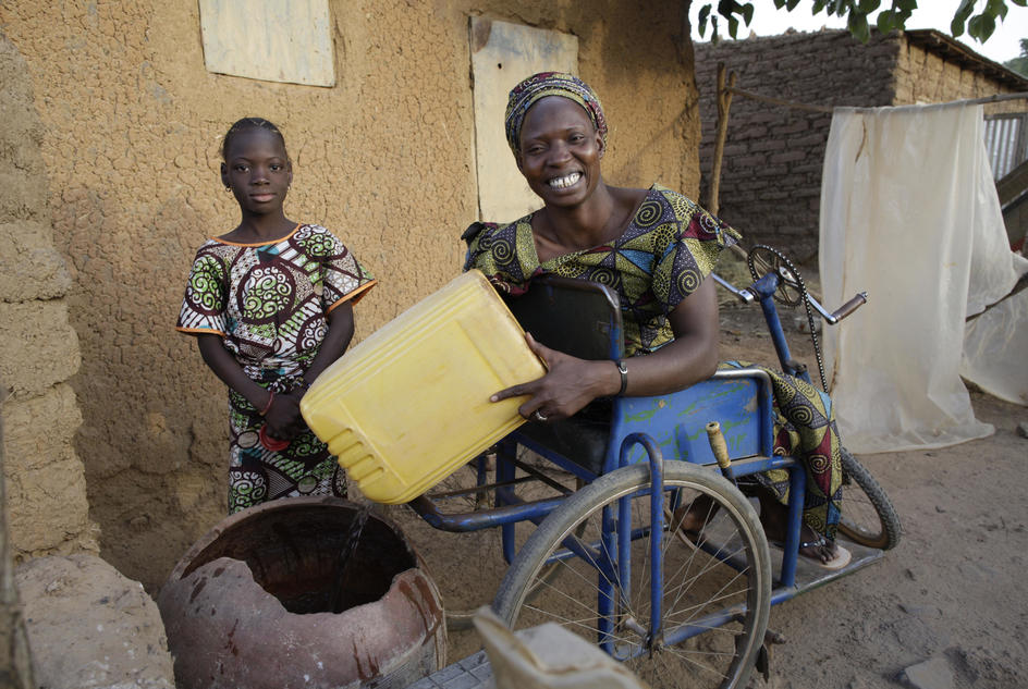 Ramata Coulibaly, member of JIGI Disability Association, and her daughter, pouring out the water they have collected, commune of Tienfala, near to Bamako, Mali.
