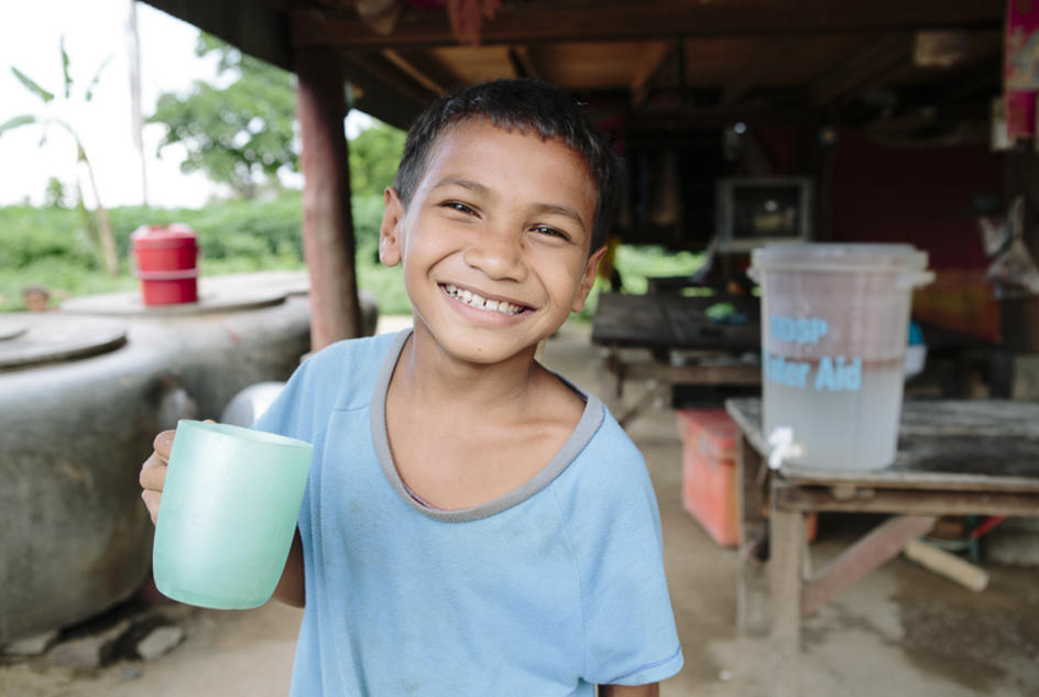 Child in Cambodia holding cups of water