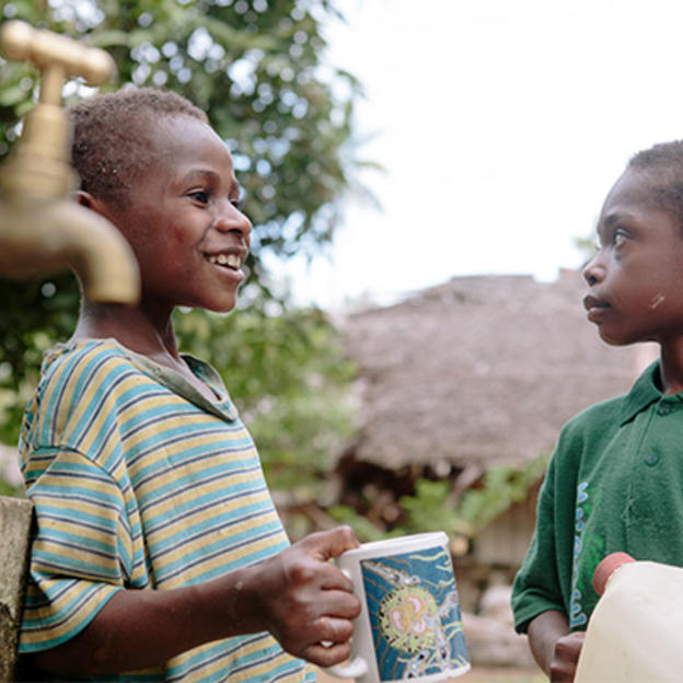 Two boys smiling while drinking from a new water point