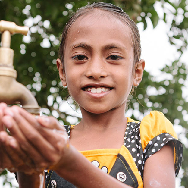 Timorese girl washing her hands under a tap.