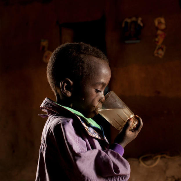 4 year old Barakot, Etalem Tinishu's young son drinks dirty water from a glass, Lahyte, Konso, Ethiopia, 2012.