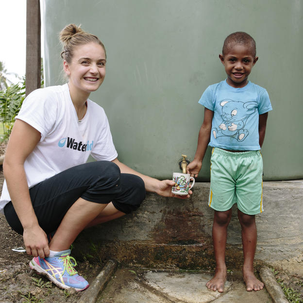 Liz Watson with water tank and girl in PNG