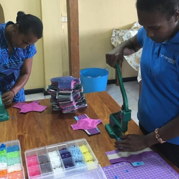 Women attaching buttons to reusable sanitary pads