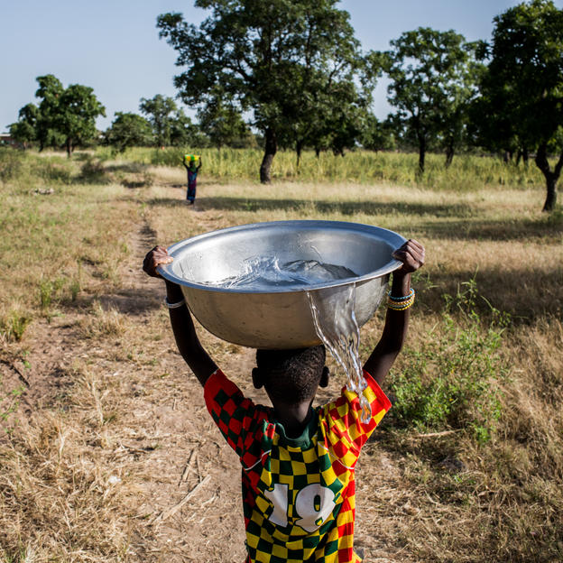 A child carries clean water drawn from a borehole in Basbedo, Burkina Faso, October 2014.