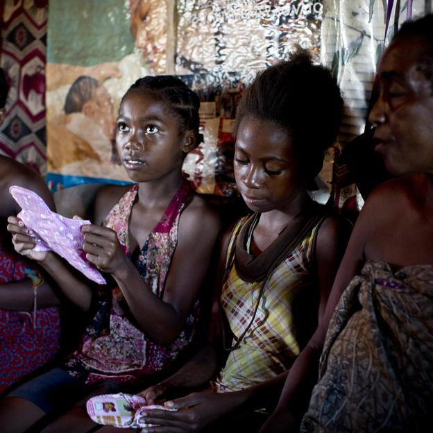 Young girls and women learn how to use a cotton sanitary towel, demonstrations done by Fanjantiana, 47, a WaterAid-trained menstrual hygiene volunteer, part of a hygiene awareness project in Madagascar. Credit: WaterAid/Kate Holt