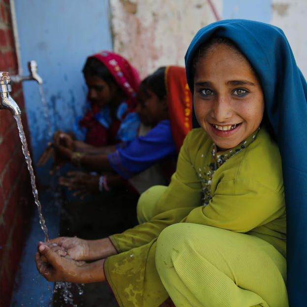 Najma washes her hands using water from a newly installed WaterAid and HM Foundation supported water and sanitation facility in Pakistan.