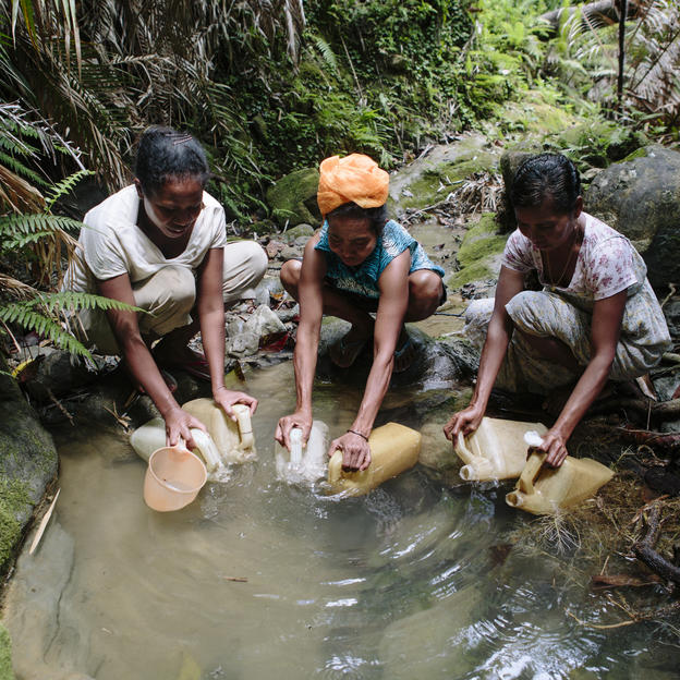 (Left to right) Emerciana Fernandos, 33, Liberatia Da Costa, 52, and Idalina Da Costa, 42, collect water from an unsafe water source far from their village of Manus in Manufahi District, Timor-Leste, 2015