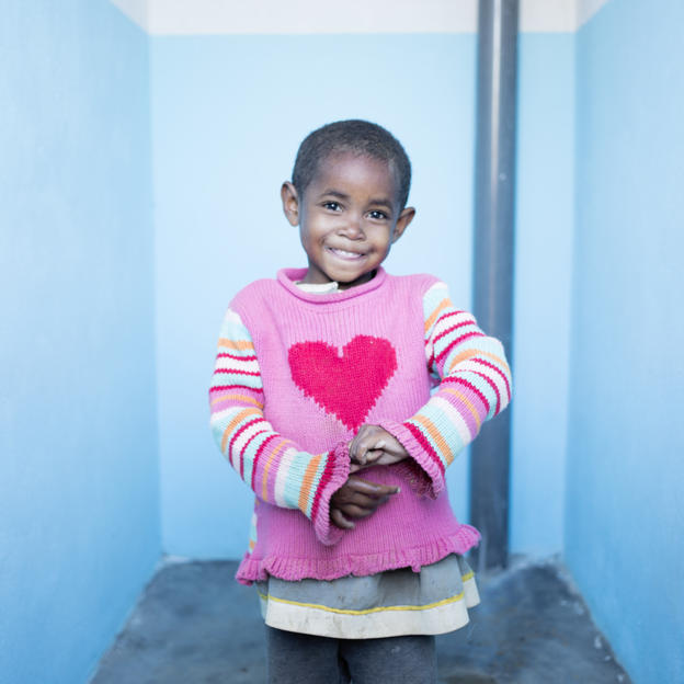 Five-year-old Henitsoa stands proudly inside her toilet block at her school in Madagascar.