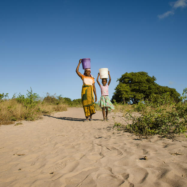 A woman and young girl carry water on their heads through a dusty desert