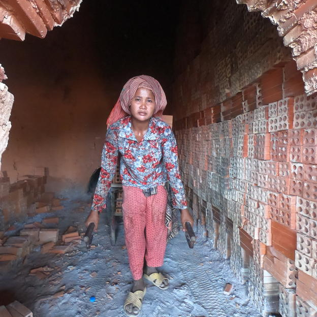 A woman carrying bricks