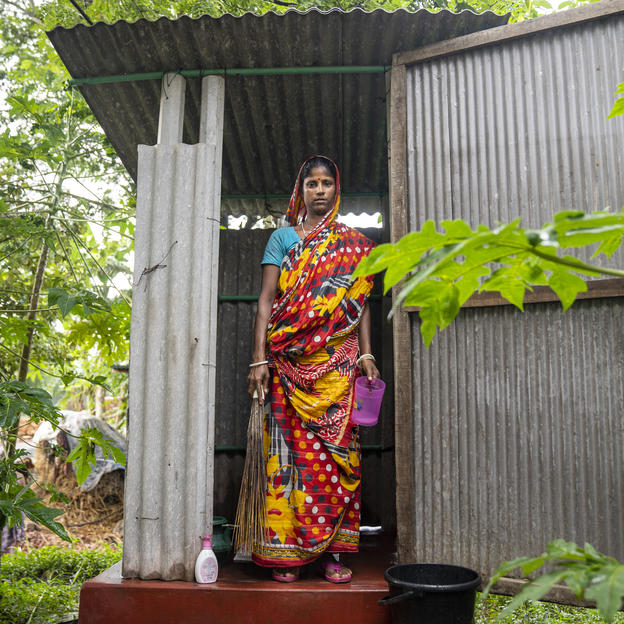 A woman stands outside a toilet