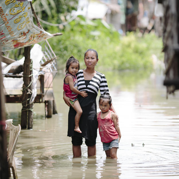 Chan, with her daughters standing in floodwater which inundates their neighbourhood