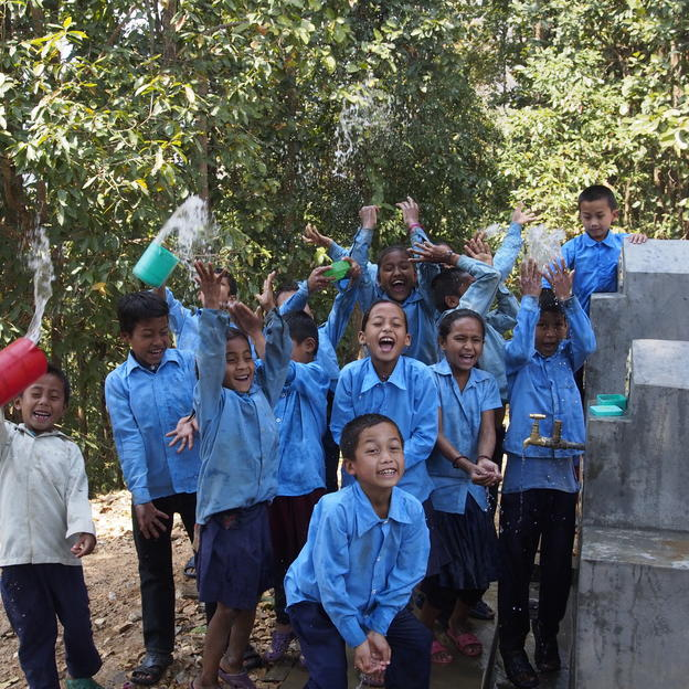 children celebrating clean water next to a tap stand