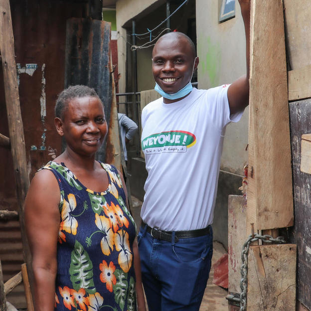 elizabeth-kisembo-56-and-her-son-christopher-tumwine-33-standing-by-their-newly-installed-gate-which-stops-people-from-passing-through-their-home-to-the-other-side-of-the-settlement-elizabeth-now