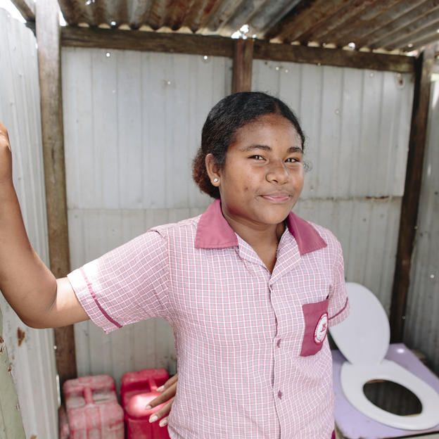 Iru, 15, student in Grade 8, stands outside her toilet at her home in the stilt village, Gaba Gaba Village, Rigo District, Central Province, Papua New Guinea