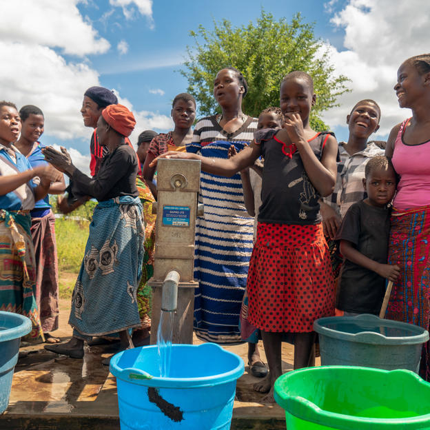 People celebrating around buckets of clean water