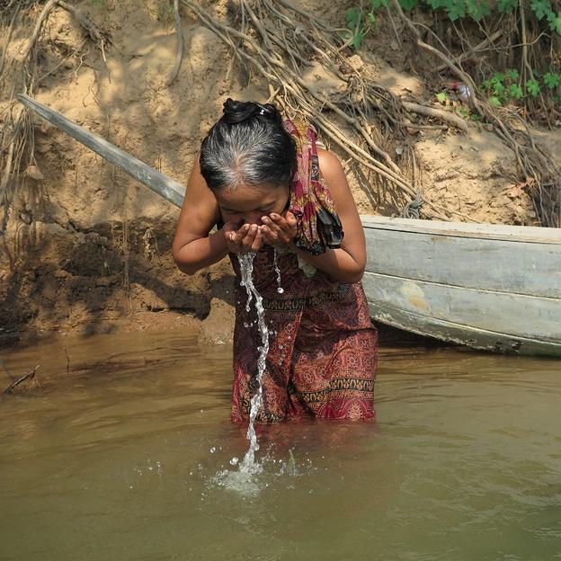 Woman drinks from the river in Cambodia
