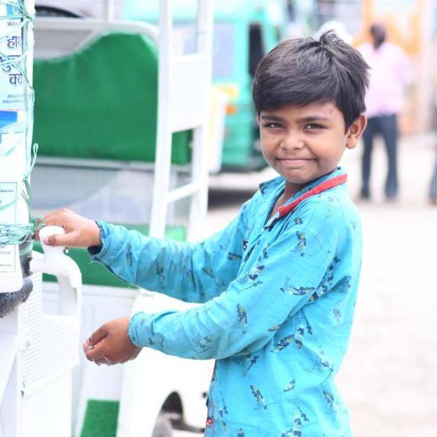 Young boy washing is hands on a rickshaw tap