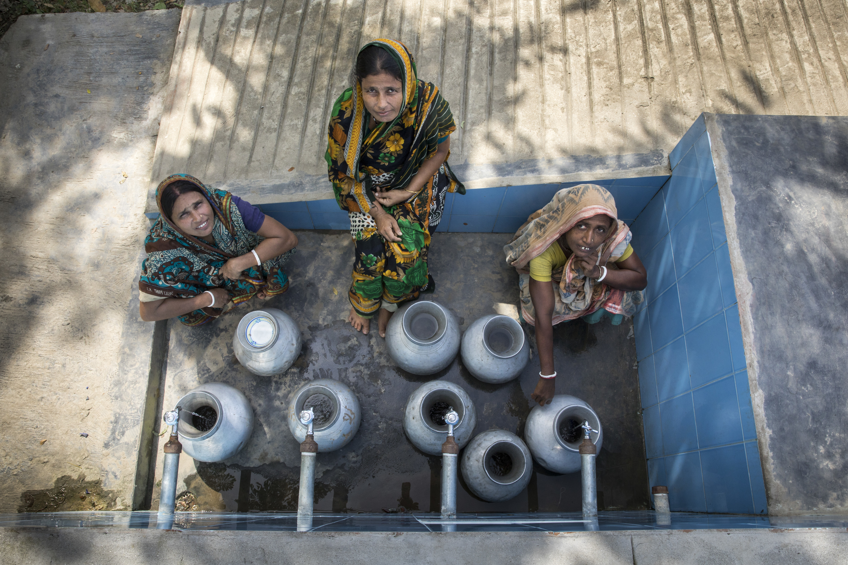 three women looking up at the camera as they fill buckets with water