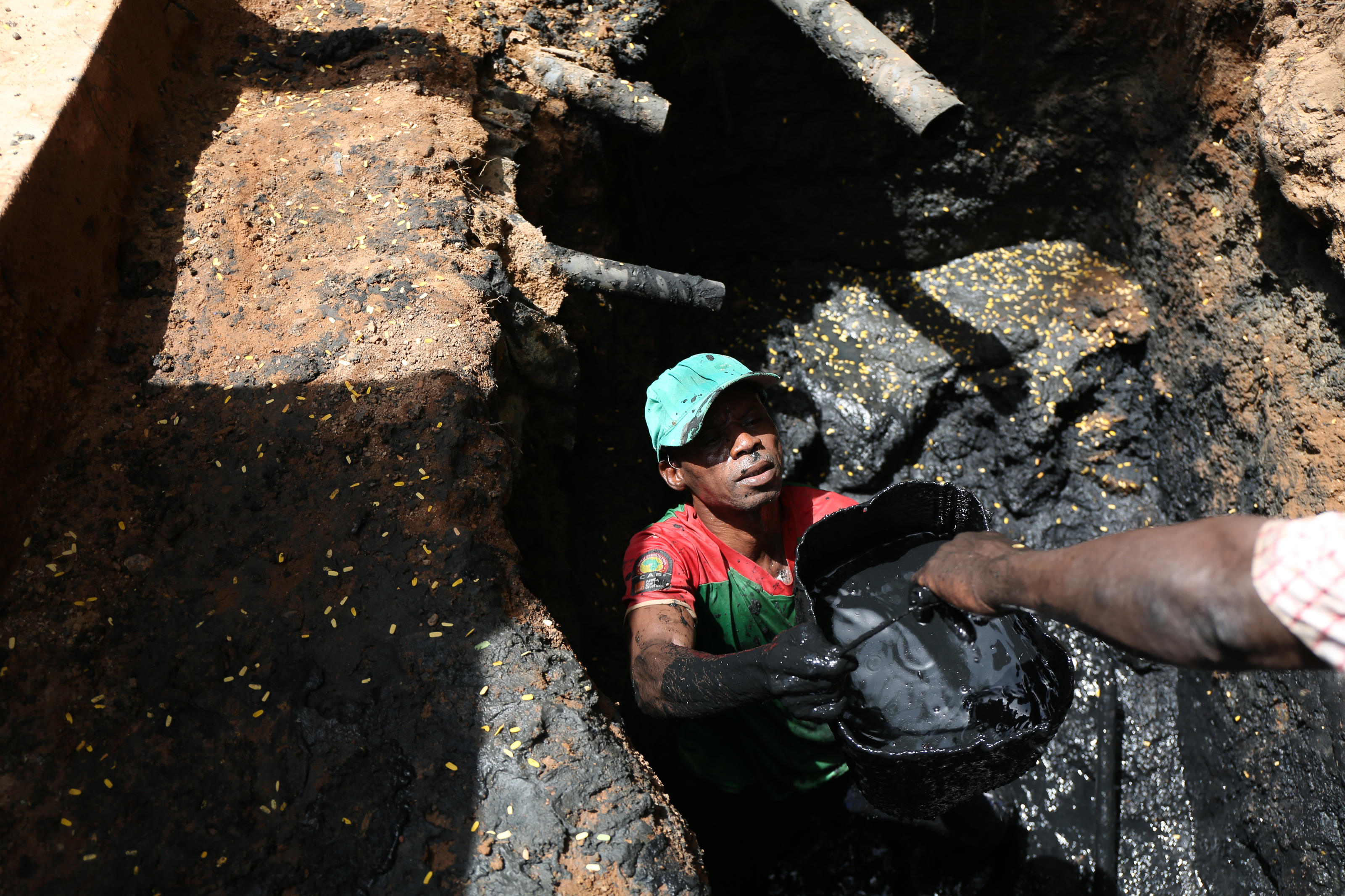 Wendgoundi passes buckets of waste out of the pit to his co-worker