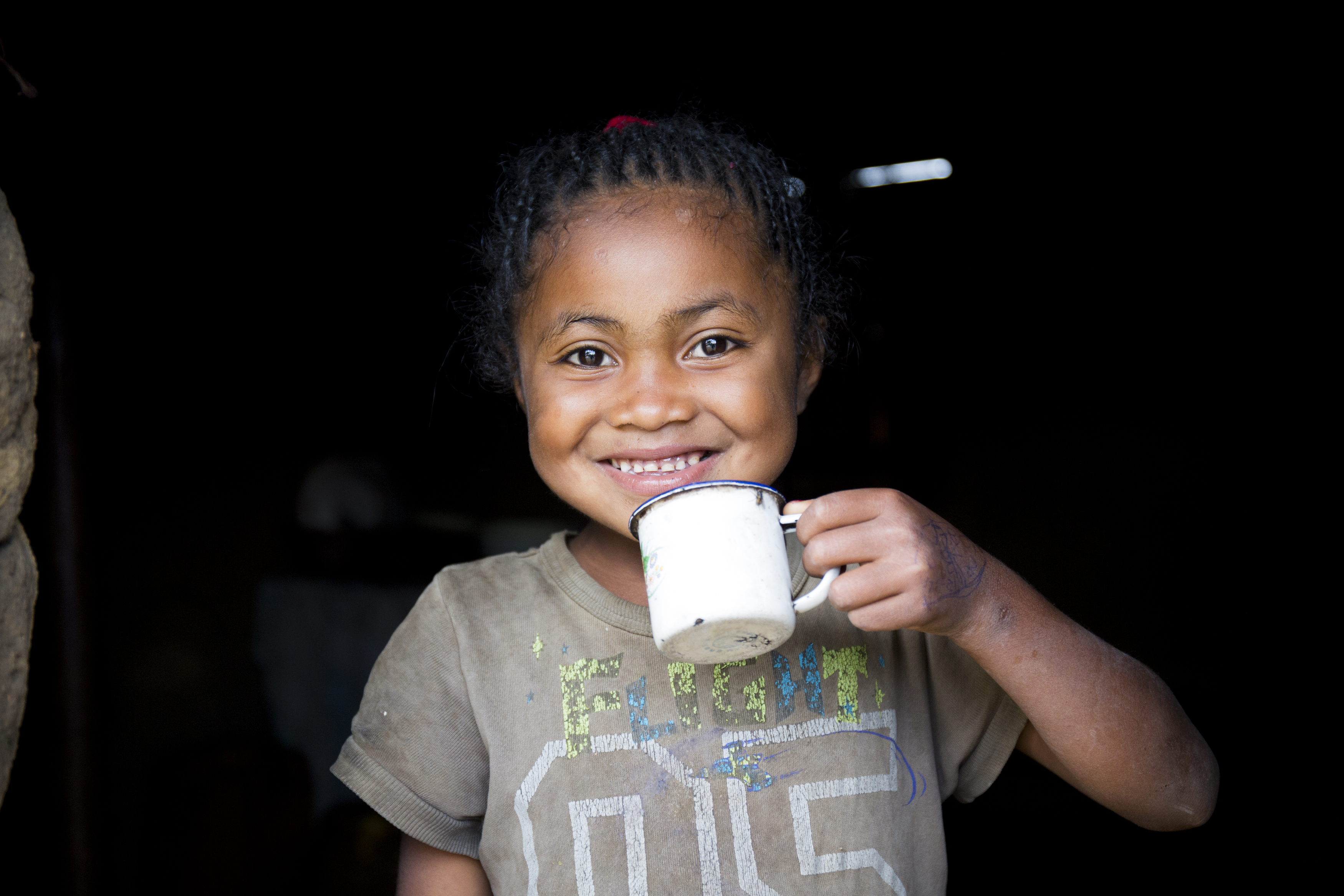 young girl smiling and drinking water from a mug