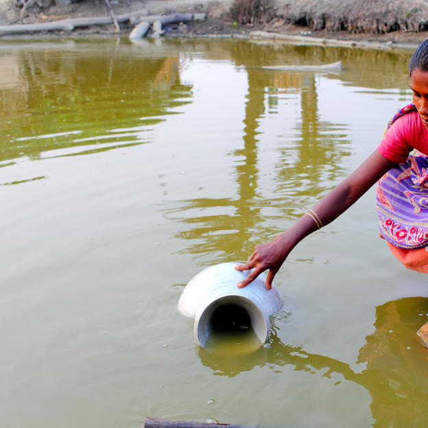Lipika Dasi Mondal collecting unsafe water from a pond that has become salinated after Cyclone Aila hit in 2009, Moshashoripur village, Koyra, Bangladesh, 2011.