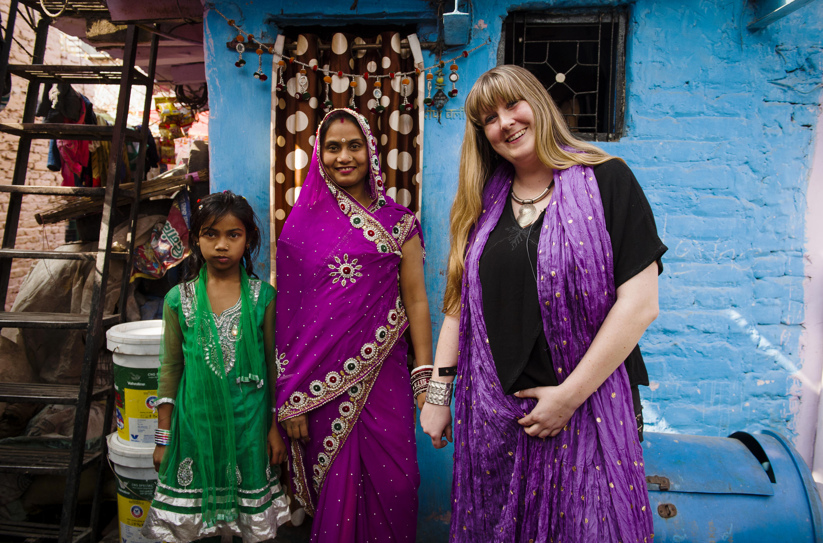 Glastonbury Festival Toilet Manager Jane Healy (right) stands with Sita Devi (centre) and her daughter Nirjala outside their house in Delhi, India.