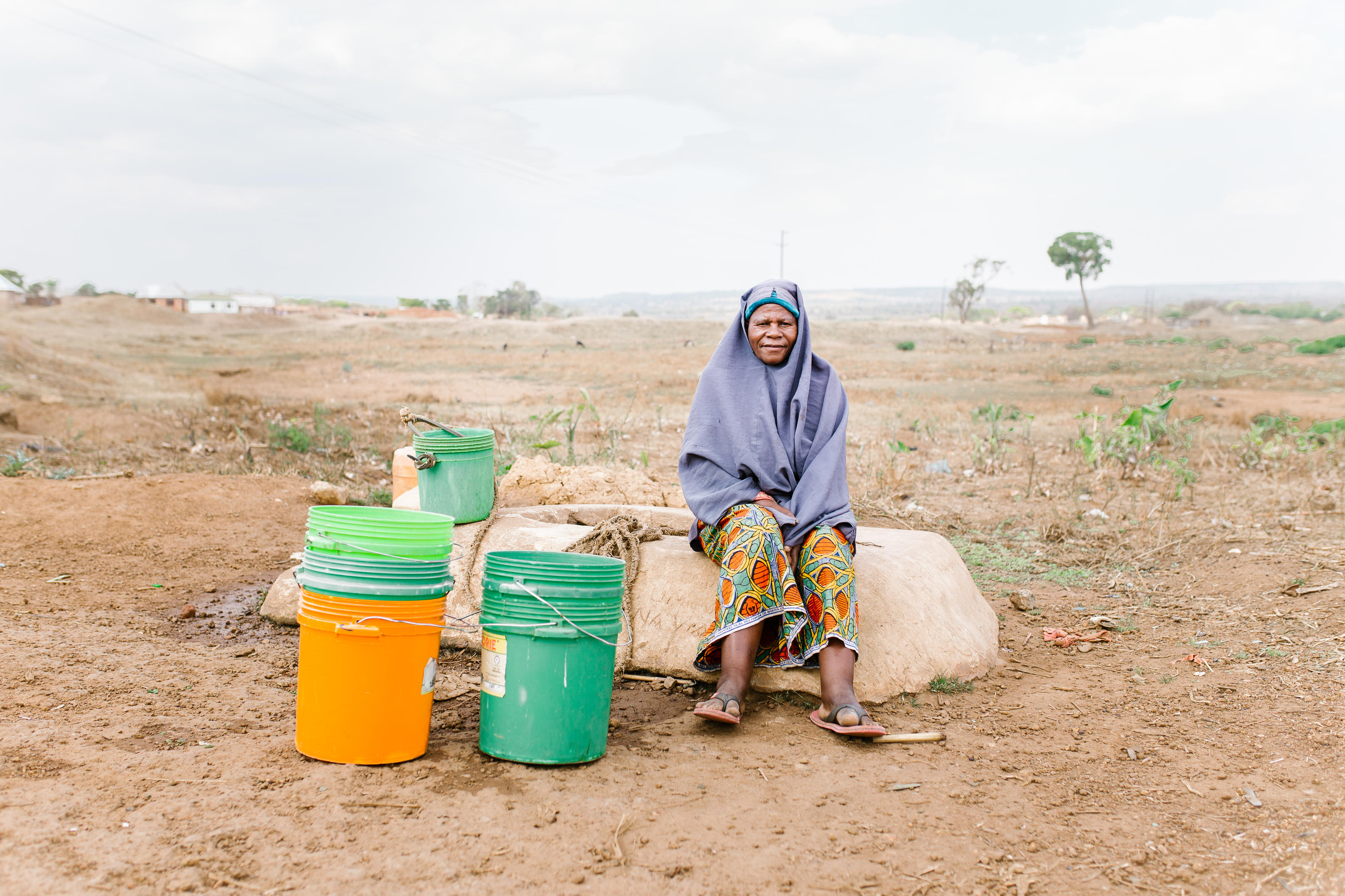 Asia Lucas, 62, sits with buckets at a privately owned shallow well on the edge of Nyarugusu. This is the closest water source to Nyarugusu Dispensary, a 15-min drive away; the well runs low in the dry season and is subject to contamination in the rainy season. Nyarugusu, Geita District, Tanzania.