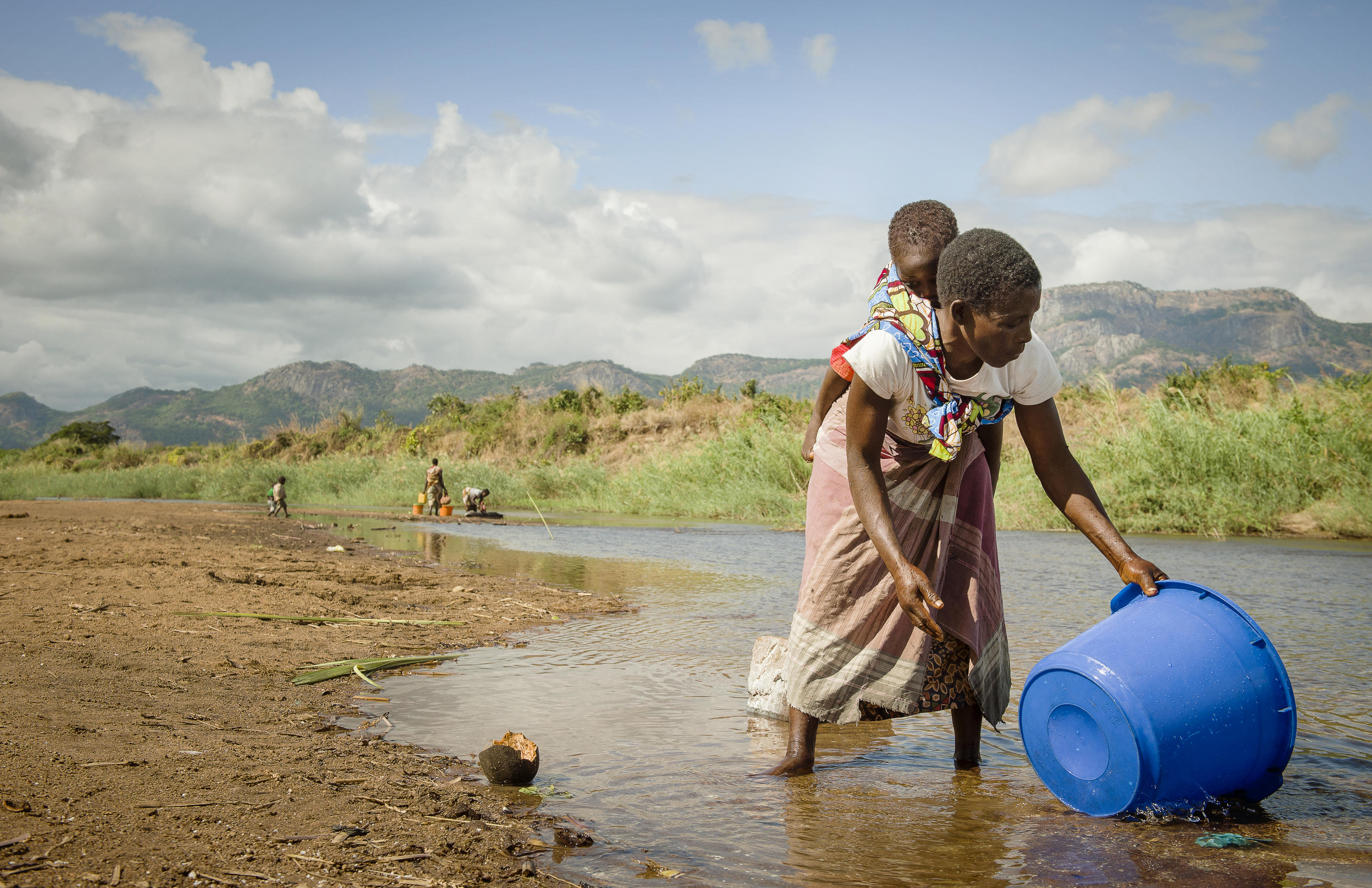 Helene Jemussene carries her baby Agostinho, 3, on her back, as she gathers water from the river near M'Mele Village, Cuamba District, Niassa Province, Mozambique. May 2017.