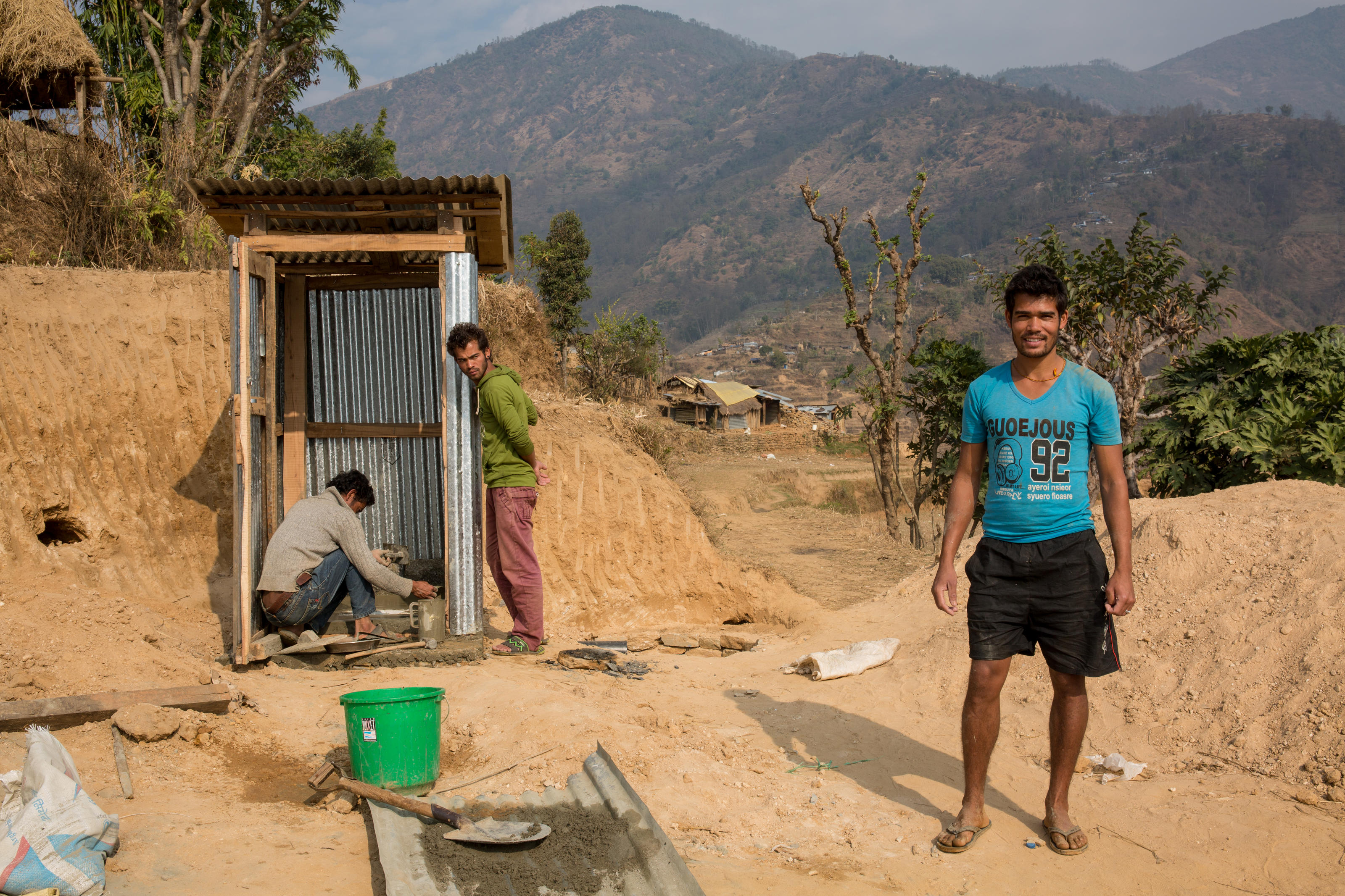 Bishwas beside his toilet. Gorkha, Nepal.