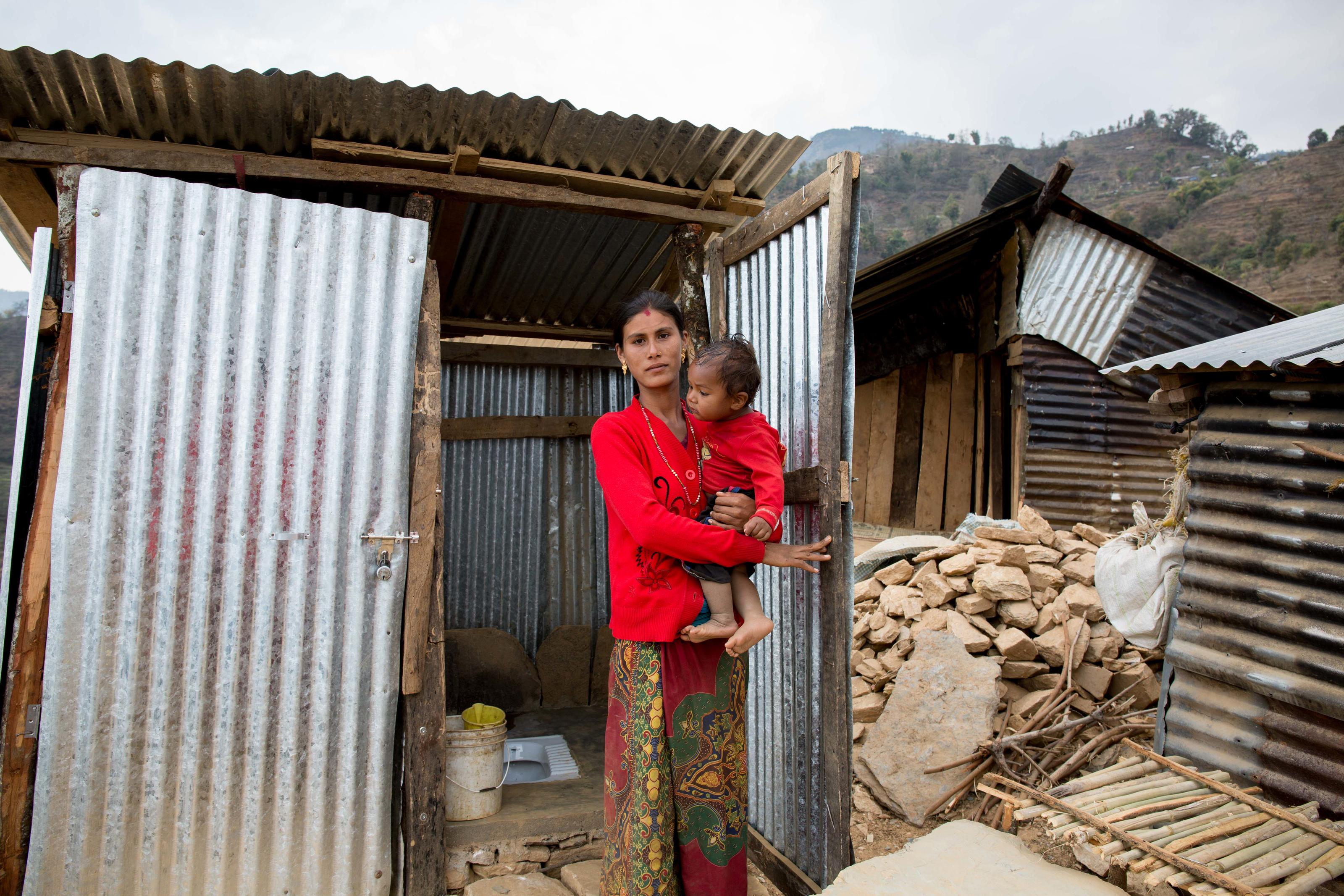 Binita with her son, standing in front of her toilet. Gorkha, Nepal.
