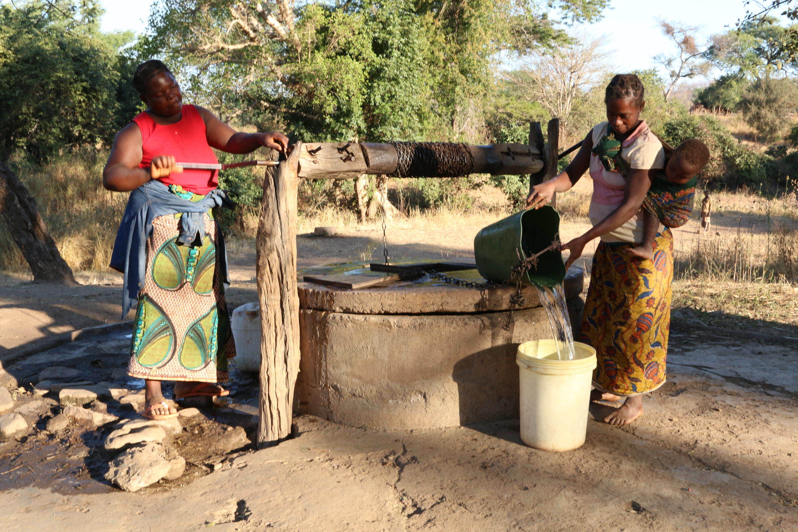 Mercy and Betina draw water from the well at Cheelo Village, Zambia