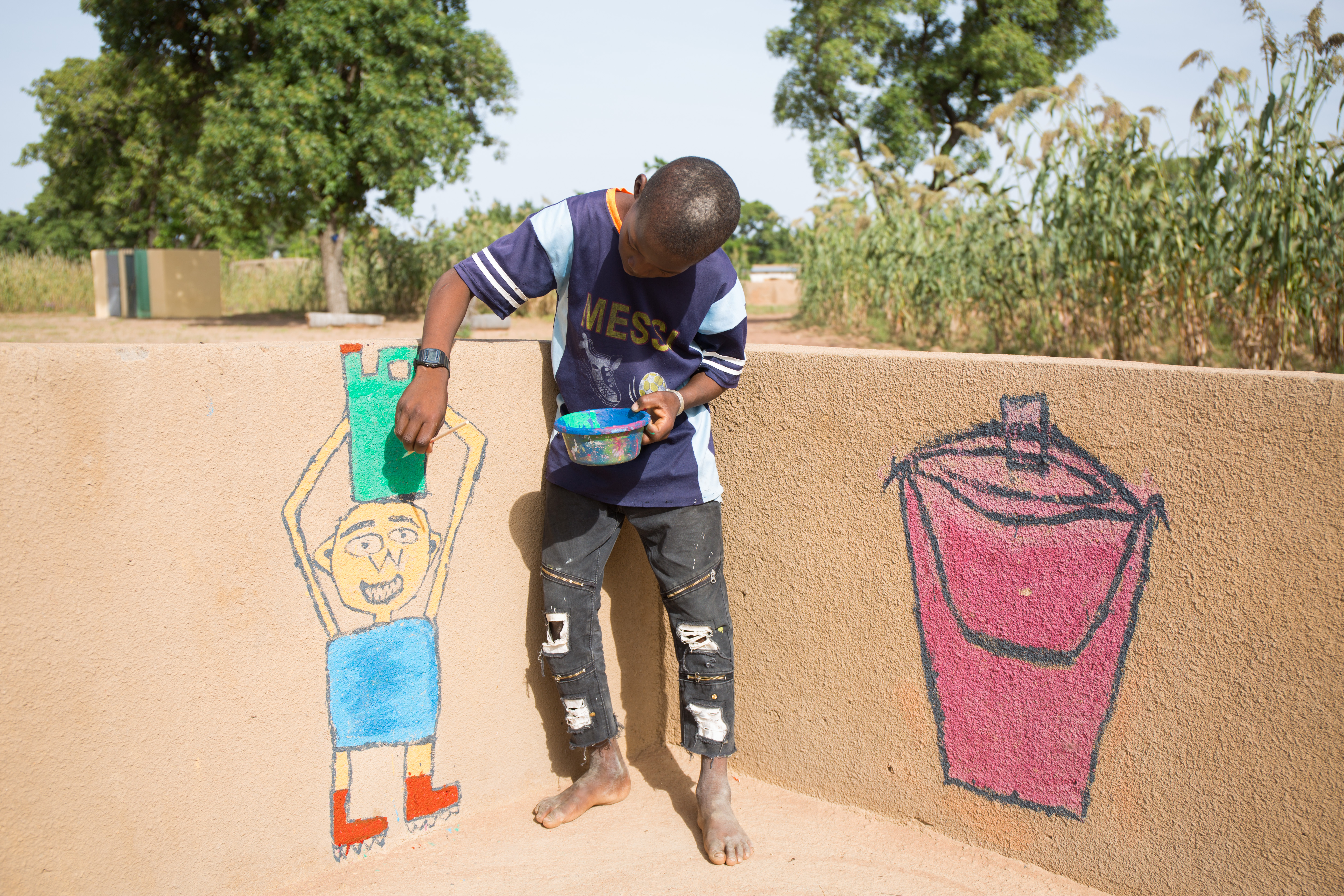 Dramane, an 11-year-old student at Wakoro school in Mali, paints a mural on the new borehole to educate his peers and community members about hygiene behaviours and attitudes to adopt or to avoid.