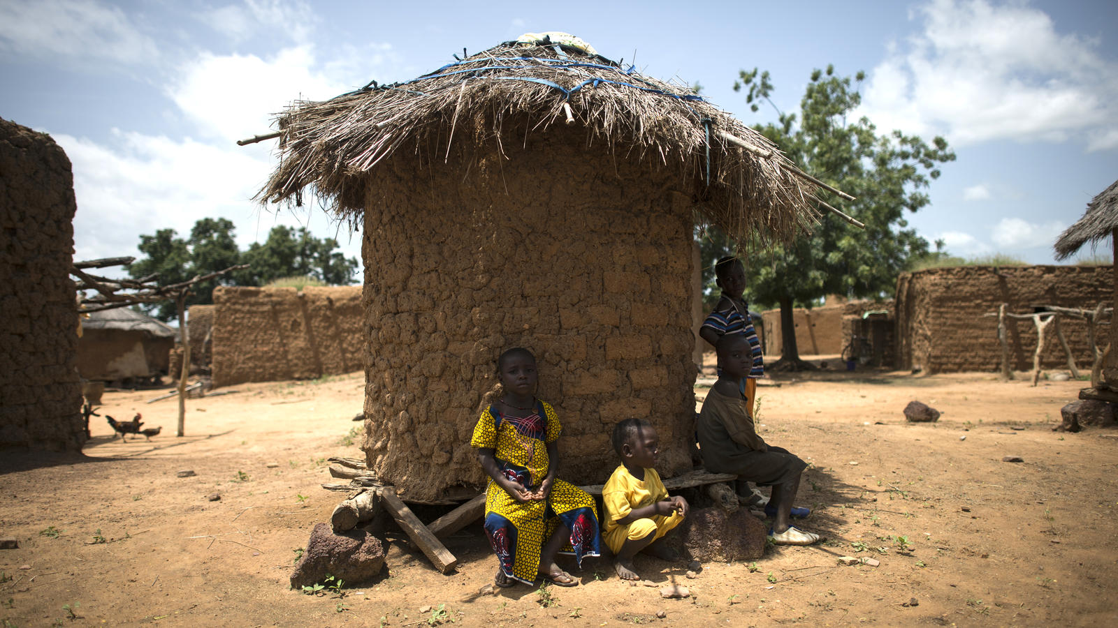 Children sit in the shade around a hut in their village in Mali.